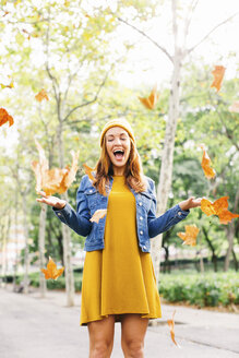 Happy young woman throwing autumn leaves in the air - EBSF001673