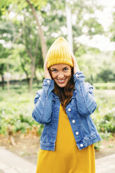 Portrait of smiling young woman putting on yellow cap - EBSF001676