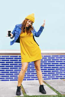 Dancing young woman wearing yellow cap and dress - EBSF001679