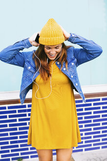 Young woman wearing yellow cap and dress listening music with earphones - EBSF001682