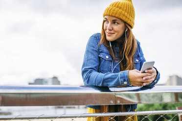 Smiling young woman wearing yellow cap listening music with earphones - EBSF001685