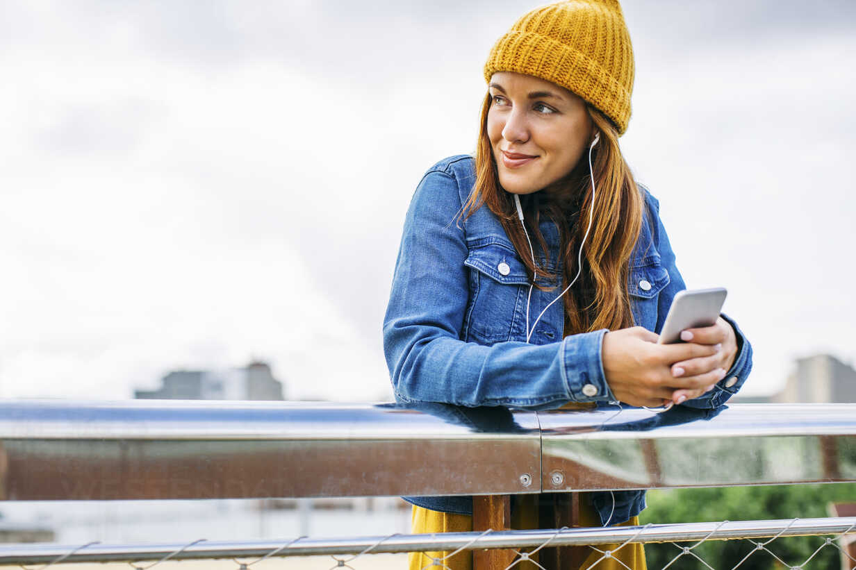 Smiling young woman wearing yellow cap listening music with earphones - EBSF001685 - Bonninstudio/Westend61