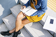 Young woman sitting on steps writing down something, partial view - EBSF001688