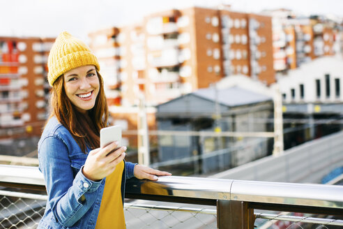 Portrait of smiling young woman with cell phone wearing yellow cap - EBSF001694