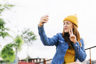Smiling young woman showing victory sign while taking selfie - EBSF001700