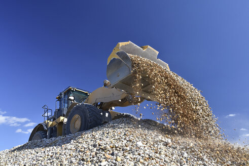 Wheel loader loading stones in gravel pit - LYF000579