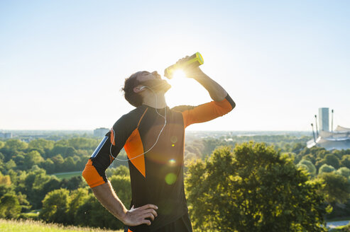 Athlete drinking from bottle in park - DIGF001078