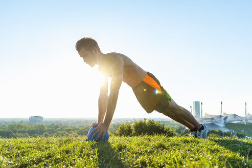 Man exercising with kettlebell on meadow in park - DIGF001081