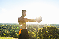 Man exercising with kettlebell outdoors - DIGF001087