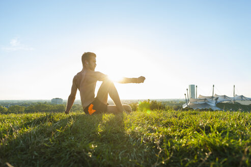 Athlete sitting on a meadow listening to music after workout - DIGF001096