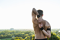 Barechested athlete stretching at sunset - DIGF001099