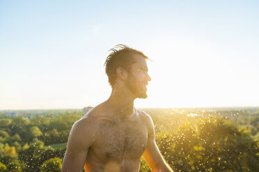 Barechested athlete shaking his wet head at sunset - DIGF001108