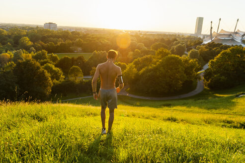 Barechested athlete on meadow in park at sunset - DIGF001111