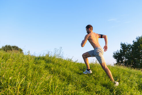 Barechested man running uphill on meadow - DIGF001114