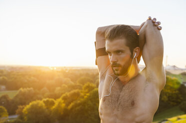 Barechested athlete stretching at sunset - DIGF001120