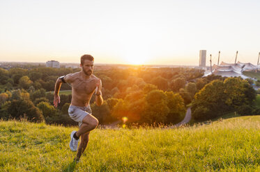 Barechested man running on meadow in park at sunset - DIGF001126
