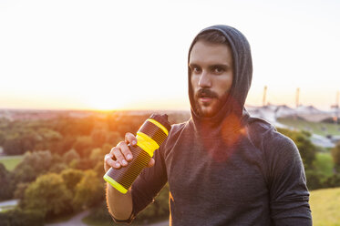 Athlete holding bottle at sunset - DIGF001129