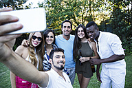 Friends taking a selfie in a garden during a summer party - ABZF001134