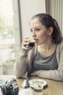 Young woman with camera drinking coffee in a cafe - TAMF000598
