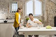 Couple in kitchen eating fruit salad - DIGF001154