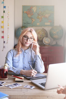 Illustrator working at home using a graphics tablet and talking on phone - RTBF000309
