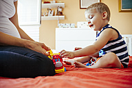 Pregnant mother and son playing on bed - ZEDF000316