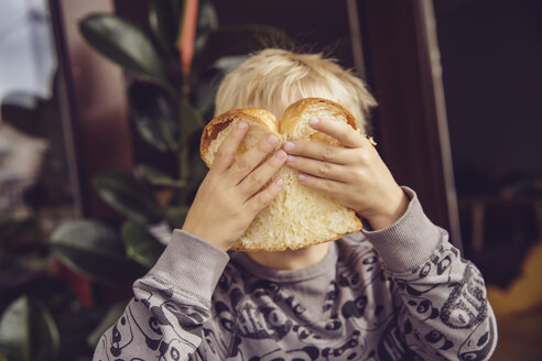 Little boy covering his face with a slice of white bread - MFF003017