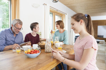 Family using portable devices during breakfast at home - RBF005161