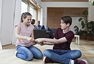 Teenage siblings fighting over tablet in living room with parents in background - RBF005167