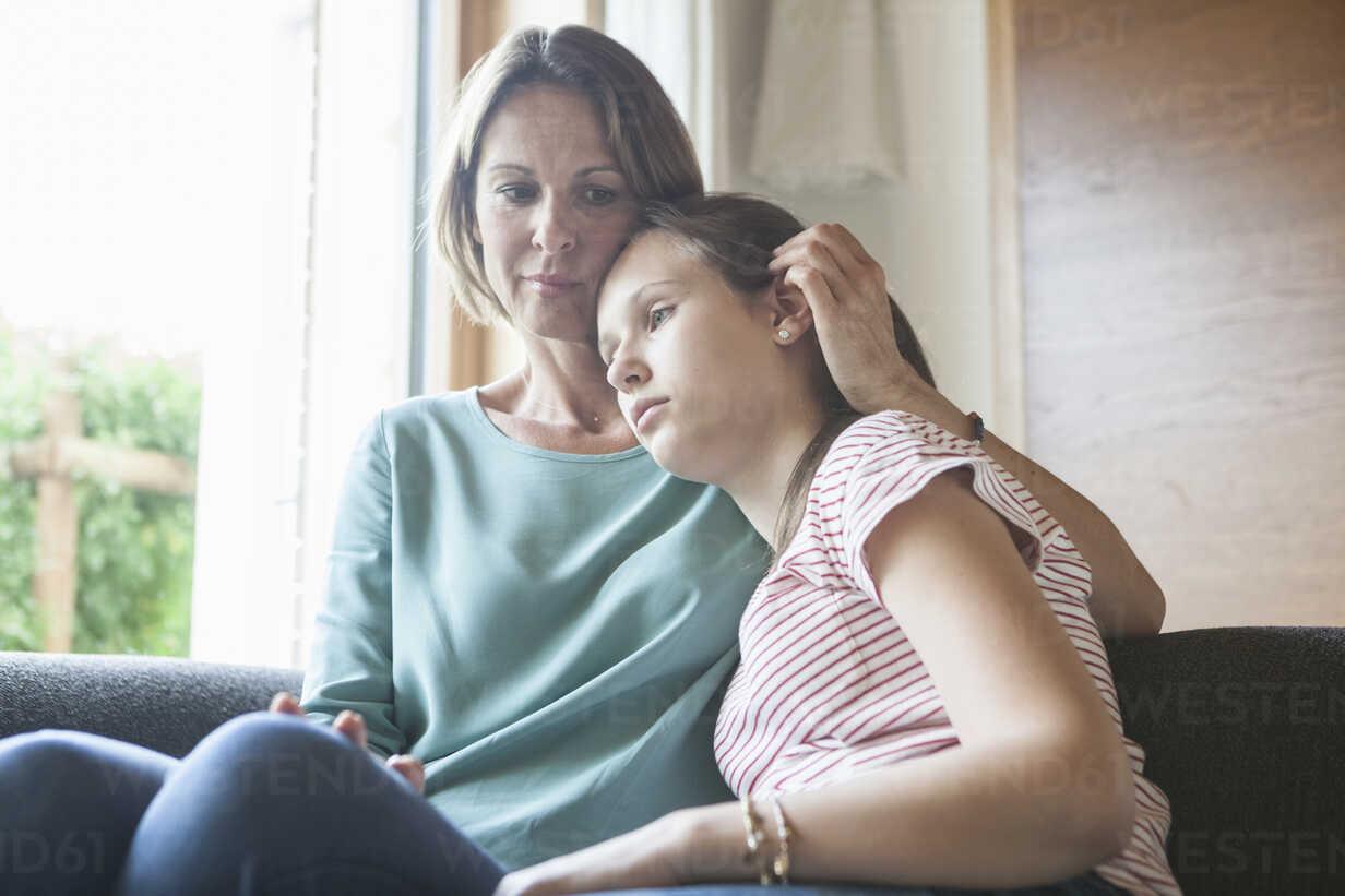 Mother comforting daughter sitting on sofa - RBF005176 - Rainer Berg/Westend61