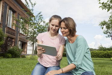Mother and daughter sharing digital tablet in garden - RBF005182