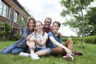 Portrait of happy family sitting in garden - RBF005191