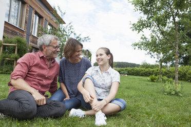 Happy family sitting in garden - RBF005194