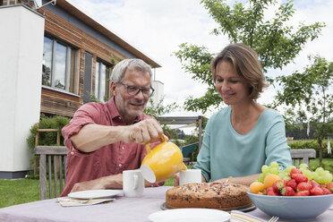 Mature couple in garden having afternoon break - RBF005197