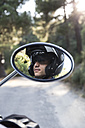 Reflection of man with motorcycle helmet in mirror of motorbike - ABZF001142