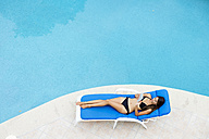 Young woman using tablet while relaxing on lounge at pool edge - ABAF002073
