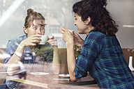 Two women sitting behind windowpane of a coffee shop drinking coffee - TSFF000080