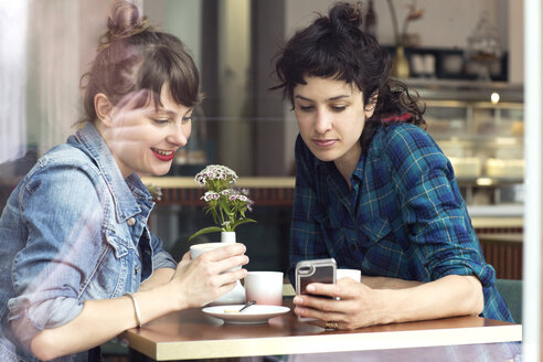 Two women sitting behind windowpane of a coffee shop looking at smartphone - TSFF000083