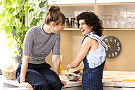 Two laughing women together in the kitchen - TSFF000098