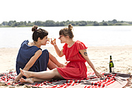 Two smiling friends sitting on the beach toasting with glasses of sparkling wine - TSFF000119