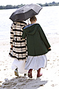 Back view of two friends walking side by side on the beach with an umbrella - TSFF000122