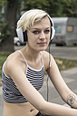 Portrait of blond young woman listening music with headphones - TAMF000628