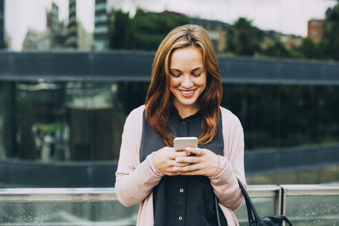 Smiling young woman looking at her cell phone - EBSF001708
