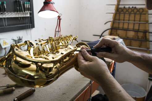 Instrument maker dismounting a saxophone during a repair - ABZF001158