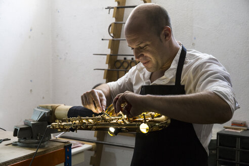 Instrument maker dismounting a saxophone during a repair - ABZF001170