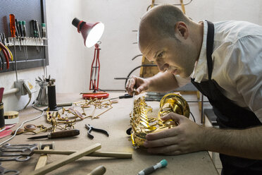 Instrument maker dismounting a saxophone during a repair - ABZF001173