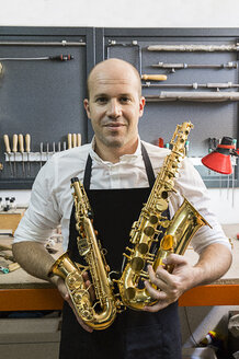 Portrait of an instrument maker holding two saxophones in his workshop - ABZF001182