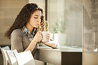 Young woman with cup of coffee in a cafe - ZOCF000138