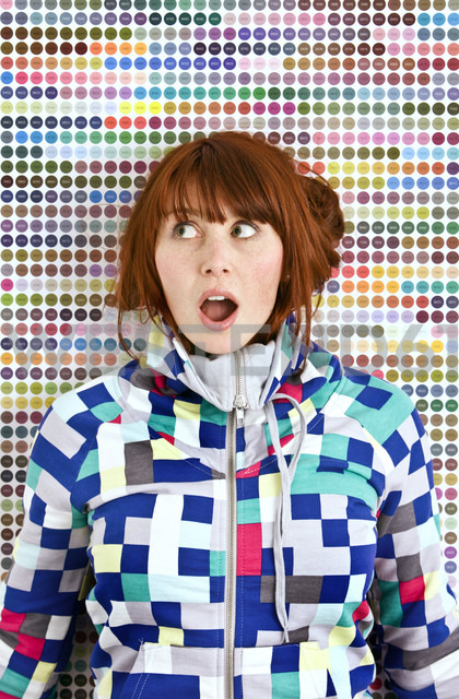 Young woman wearing patterned jacket in front of dotted wall - MFF003024