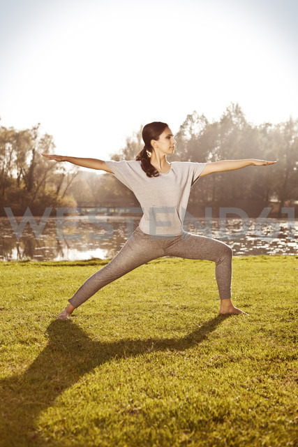 Woman standing in Virabhadrasana position at lakeside - MFF003057